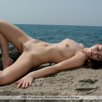 Slender girl with big perky breasts naked at the beach